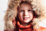 Smiling child in fur hood and orange winter jacket. children