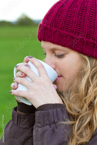 Junge Frau mit einem Heißgetränk in der Natur