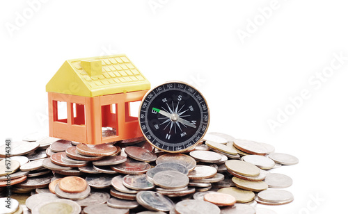 House model and compass on coins background