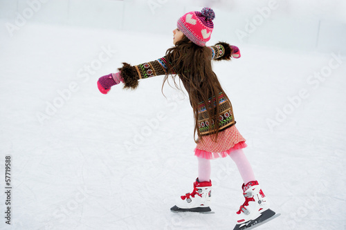 Adorable little girl on the ice rink