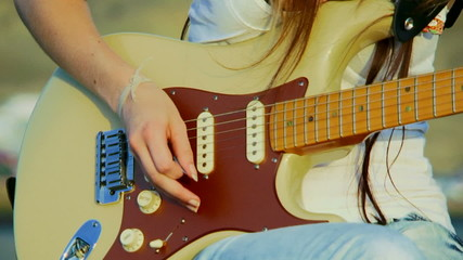 Girl playing guitar. Close-up