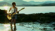 Guitarist standing in a water and playing