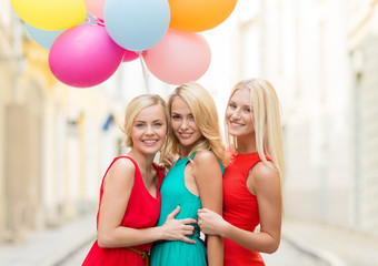 beautiful girls with colorful balloons in the city