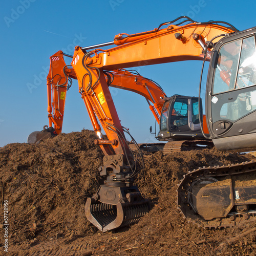 Two orange excavators