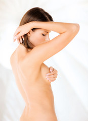woman checking breast for signs of cancer