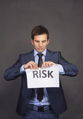 Businessman tearing paper which written risk word