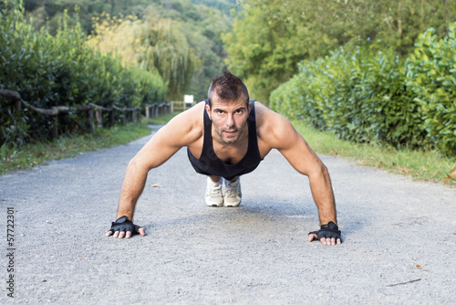 Muscular man doing push up in the park.