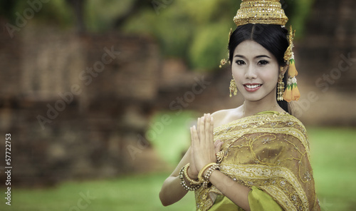woman performing typical thai dance with thai style temple backg