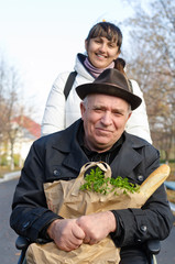 Smiling senior man with a bag of groceries