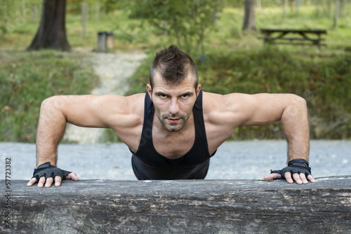 Man doing pushups on wooden log.