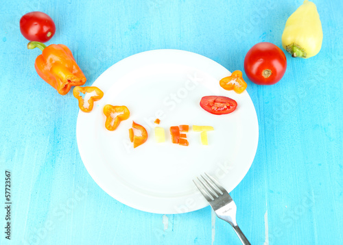 Word diet lined vegetables on plate on wooden table close-up
