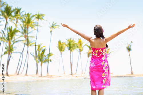 Praising happy freedom woman on beach in sarong