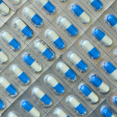 Blue and white capsules in transparent strips.