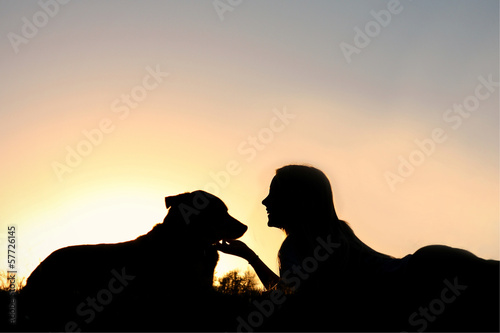 Silhouette of Girl Laying in the Grass with Her Dog