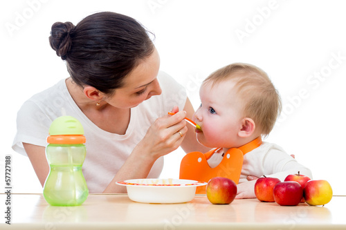 young mother spoon feeding her baby girl