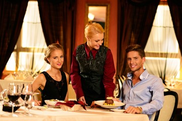 Beautiful young couple in restaurant and waitress bringing meal