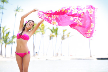 Beautiful woman in bikini on beach waving scarf