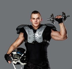 American football player holding helmet and dumbbell