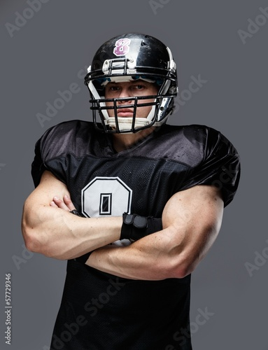 American football player wearing helmet and black jersey with nu