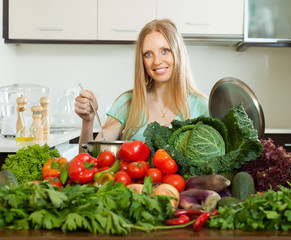 happy   woman cooking with heap of raw vegetables