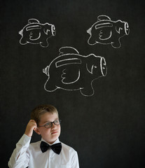 Business boy with flying piggy banks on blackboard background