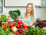 happy housewife with raw cabbage and  vegetables