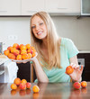 young blonde housewife with heap of apricots t domestic kitchen