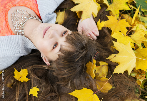 Beautiful girl with long dark hair in autumn park