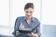 Cheerful businesswoman writing in her diary sitting at her desk