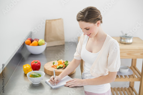 Happy beautiful woman standing in her kitchen writing on a noteb