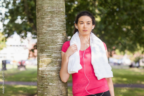 Young sporty woman leaning against a tree
