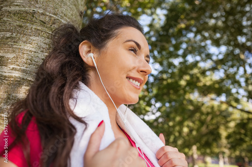 Happy brunette young woman leaning against tree