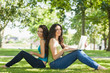 Two cute brunette women sitting on a lawn smiling at camera