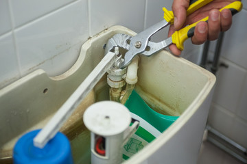 Close up of hand repairing toilet