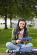 Smiling brunette student using tablet sitting on bench