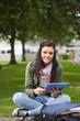 Smiling brunette student using tablet sitting on bench