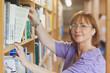 Mature female librarian taking a book off a shelf