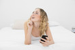 Pretty day dreaming blonde lying on bed using smartphone