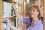 Mature female librarian taking a book off a shelf
