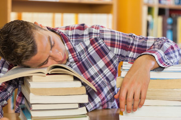 Tired handsome student resting head on piles of books