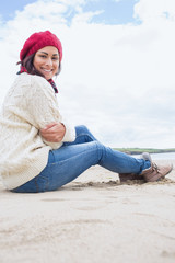 Smiling woman in stylish warm clothing sitting on beach
