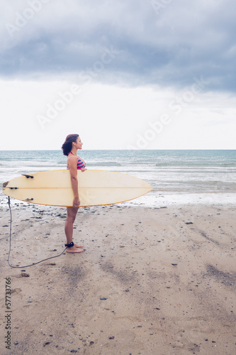 Side view of a woman carrying surfboard on beach