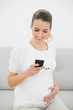 Gorgeous pregnant woman messaging with her smartphone while hold