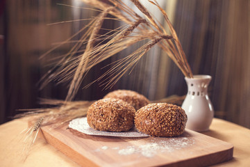 Fresh bread and wheat ears on the wooden table