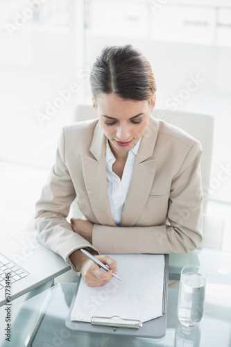 Young concentrated businesswoman writing on a clipboard