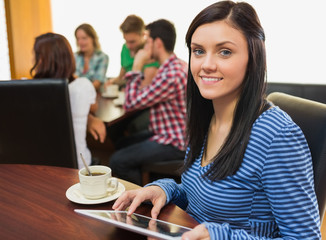 Smiling female with coffee using tablet PC at  the coffee shop