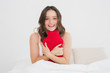 Smiling woman with a hot water bottle in bed
