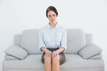 Displeased well dressed woman sitting on sofa