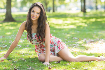 Stylish smiling brunette sitting on grass