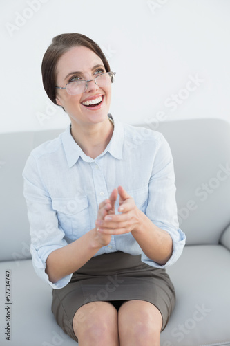 Smiling well dressed woman clapping hands on sofa